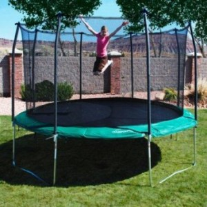 child on trampoline in backyard